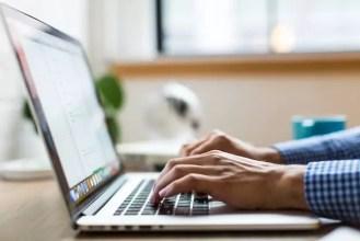 Zwei Hände tippen auf der Tastatur eines Laptops