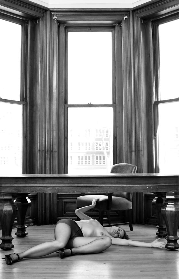 a twisted woman beneath desk