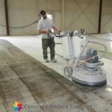 A man concrete grinding off carpet glue