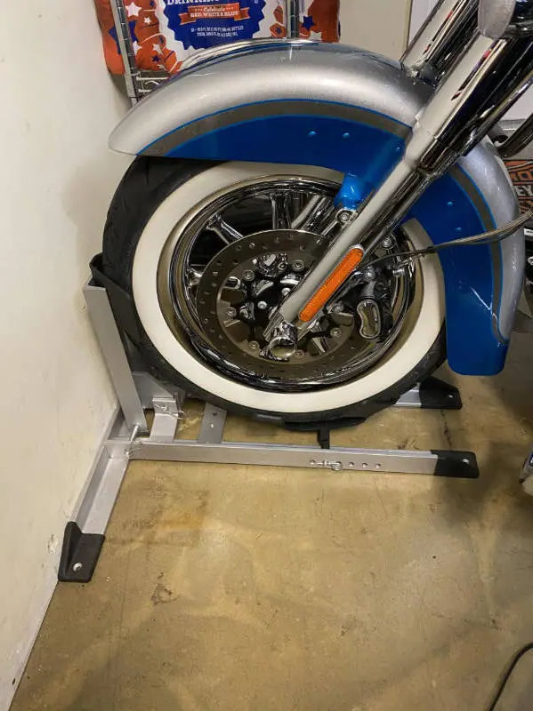 Closeup of blue motorcycle in a wheel chock