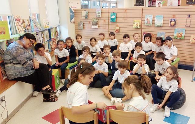 In der Bibliothek der deutschen Schule Sankt-Thomas-Morus: Kinder lesen ihren Mitschülern aus einem Buch vor.