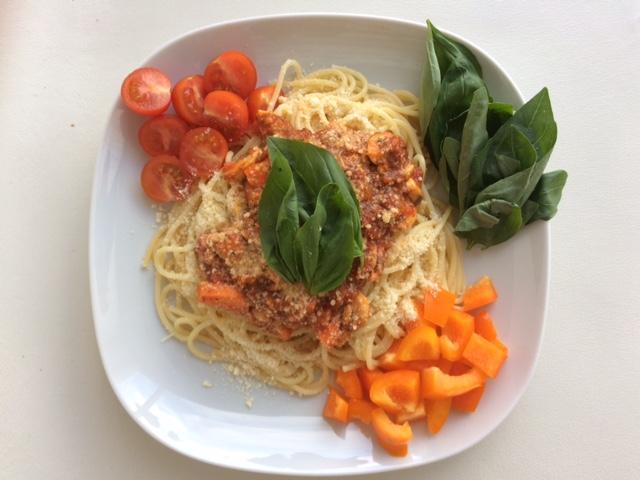 Spaghetti saus tomat wortel dan jamur disajikan dengan taburan keju, paprika, daun basil, dan tomat.