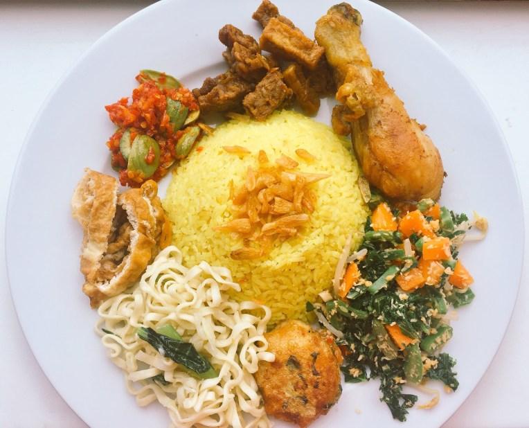 Nasi kuning dengan pelengkap ayam goreng,orek tahu tempe, sambel pete, telur dadar, mie kuning, perkedel, dan sayur urap