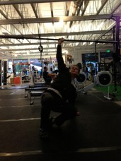 step two: get up onto your knee while keeping the barbell over your head.
