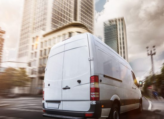 A white van is sharply in focus in the foreground driving away from the camera; the background is heavily motion blurred with skyscrapers and trees.