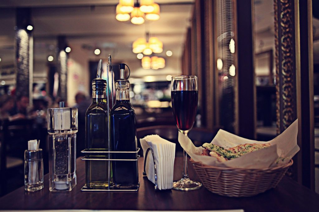 The foreground shows various table items at a restaurant. There is a sugar holder, salt and pepper, vinegar and olive oil, napkins, a glass of merlot wine and a small basket of bread.