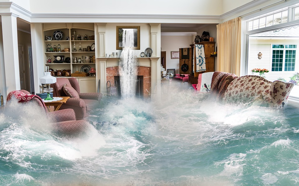 A lounge filled with furniture, that is flooding with water emerging from a picture of a waterfall above the fireplace.