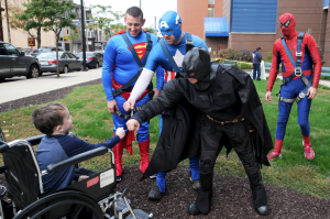 James Howe, 5, of Moon, gets a fist-bump from Batman and Captain America this morning as the superheroes descended on Children's Hospital to give the building a thorough window washing. - Photo Credit Nate Guidry/Post-Gazette