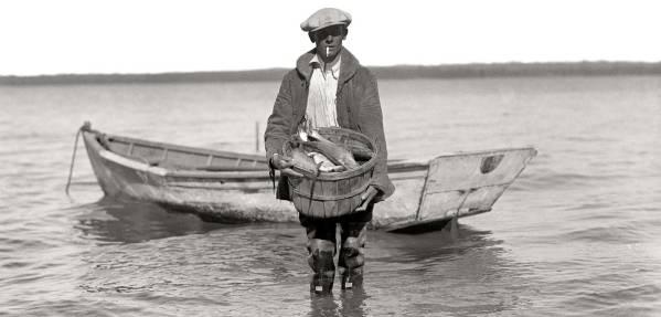 Vintage image of fisherman holding a basket of fish