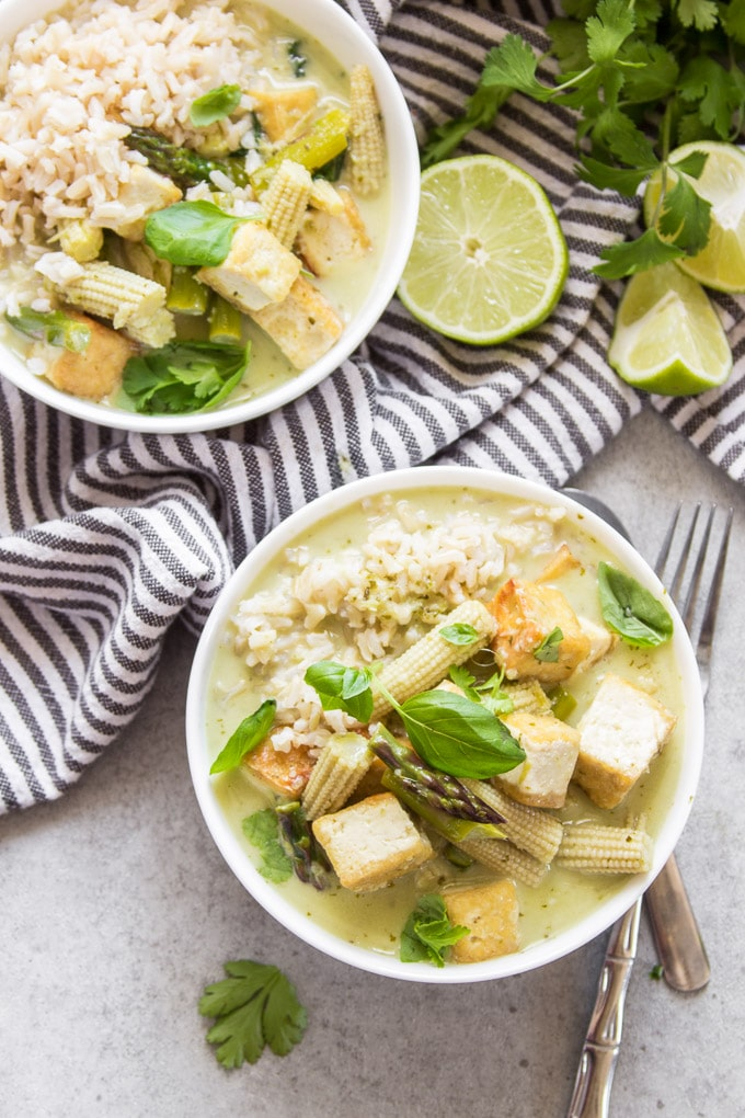 Two Bowls of Vegan Green Curry with Napkin and Lime Wedges