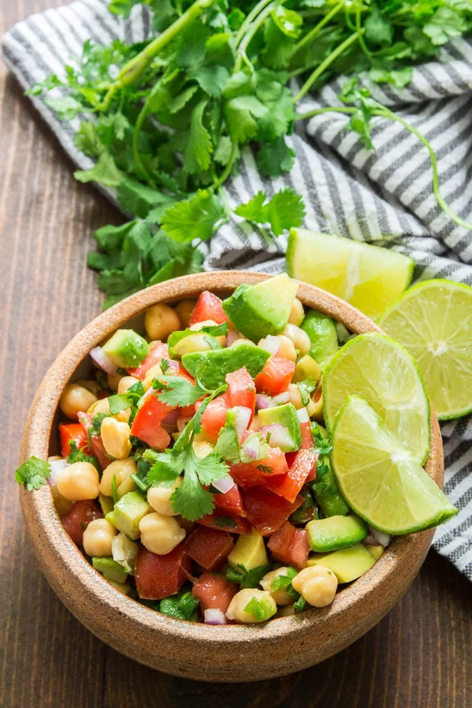 Vegan Ceviche in a Stone Bowl with Fresh Cilantro, Lime Slices and Fresh Cilantro in the Background