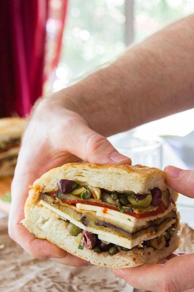 Pair of Hands Picking up a Slice of a Vegan Muffaletta