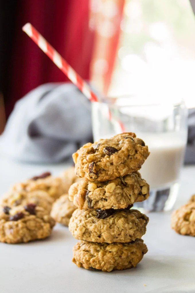 Stack of Vegan Oatmeal Raisin Cookies with Drinking Glass in the Background