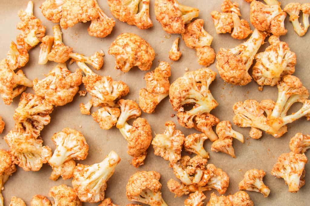 Cauliflower Florets Coated with Spices on Parchment Paper