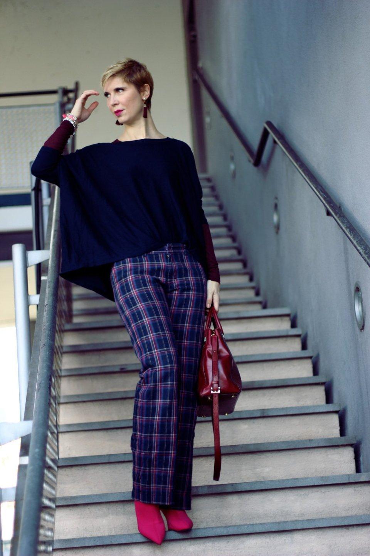 Dieses Foto illustriert einen Beitrag über den Shopping-Club Zalando Lounge: Es zeigt Conny Doll Lifestyle in einer Karohose in blau, lila und burgunder Tönen außerdem Sockenstiefeletten und einen Oversized-Pullover, ein farbenfroher Look für den Herbst 2017