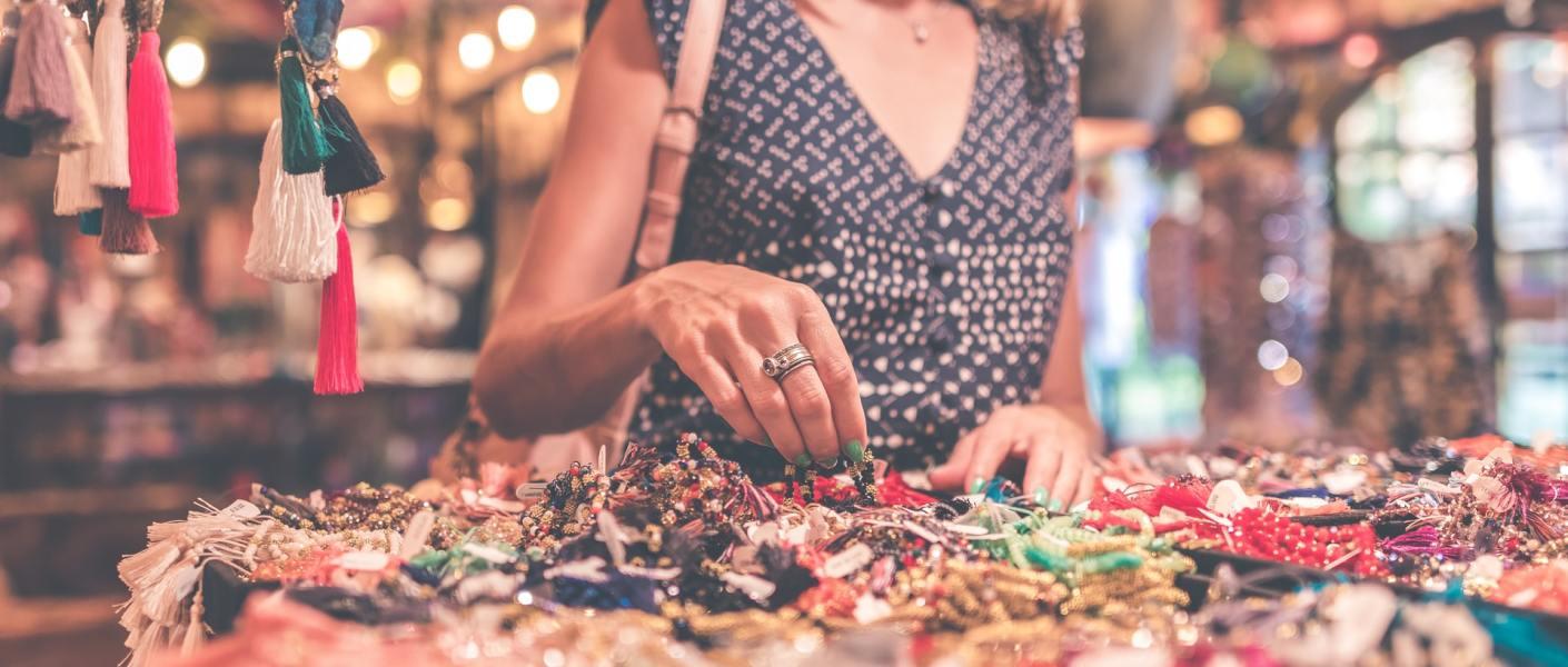 donna in un mercato artigianale che sceglie da un banco dei gioielli