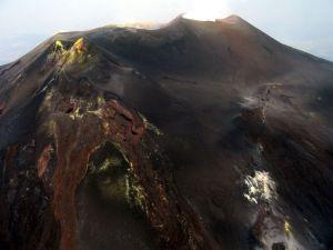 """Figura 4 – Visione aerea, da Est, dell'area sommitale dell'Etna. A sinistra, si nota il cono del Cratere di Sud-Est, """"bucato"""" in corrispondenza della sua base orientale dalla bocca eruttiva che costruirà, dal 2011 in poi, il Nuovo Cratere di Sud-Est. A destra, si osserva la frattura eruttiva che ha alimentato l'eruzione laterale del 2008-2009. Foto: Marco Neri."""
