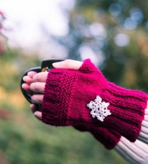Knitted fingerless gloves with crochet snowflake motif