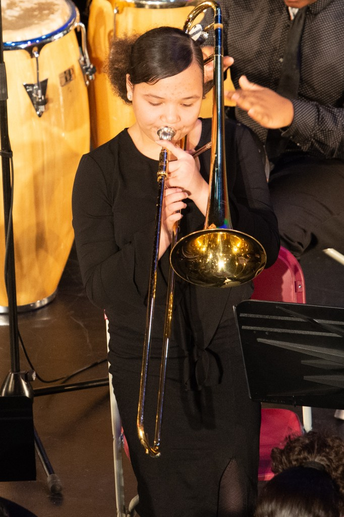 A young woman with light skin and a puffy pony tail plays trombone during a performance at the Strand Theatre in 2019
