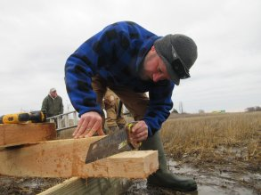 Ben W. cuts a lap joint in the top of a 19' cedar post. photo by Wayne Russell