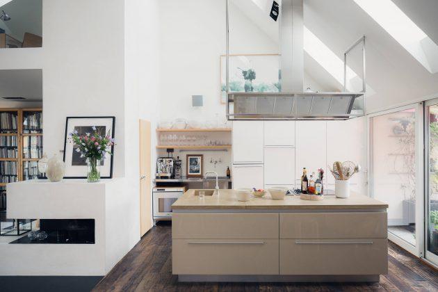 cuisine moderne de style loft ouverte sur le salon avec une grande hotte d'aspiraition