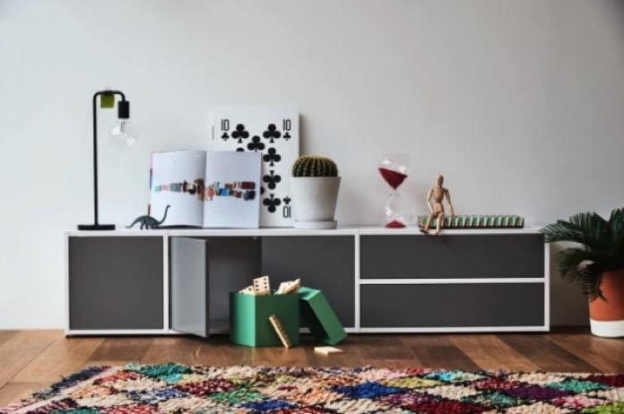 Etagère blanche et grise avec tiroirs de rangement. Parquet et tapis avec losanges multicolores.