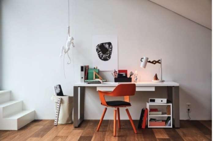 Espace de travail tout en blanc avec chaise design orange sur parquet