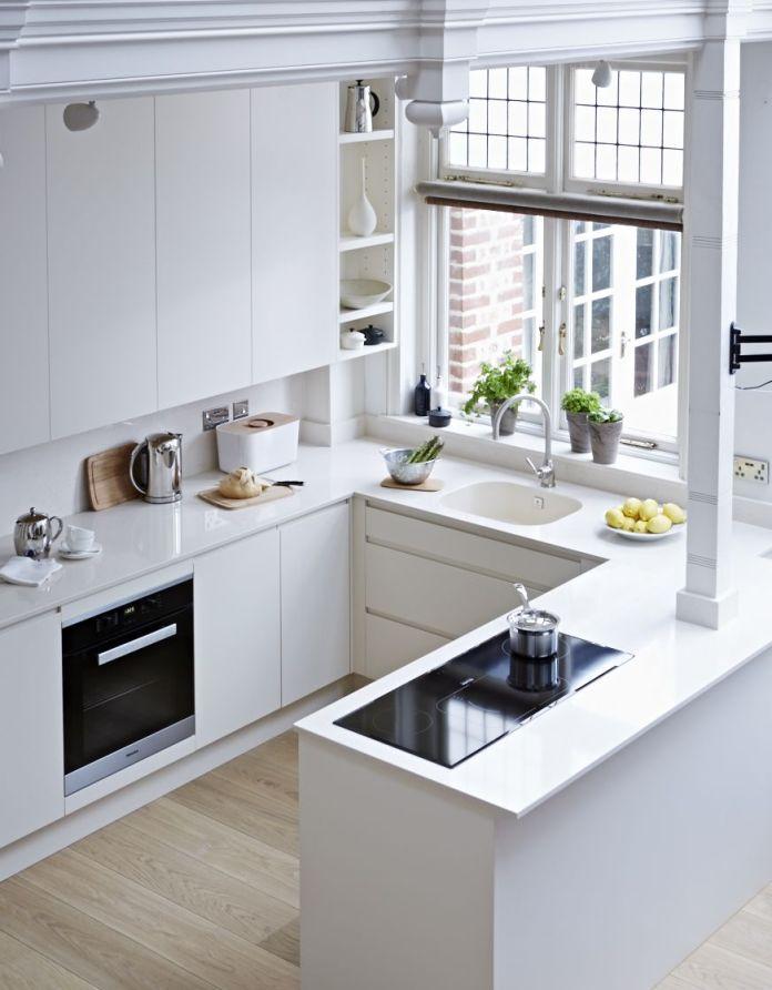 Vue plongeante sur une une cuisine blanche en U très moderne.