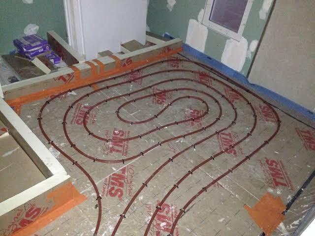 Installation d'un plancher chauffant dans une salle de bains.