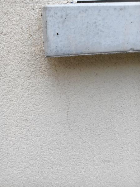 de petites fissure sur une façade à la suite d'infiltrations d'eau