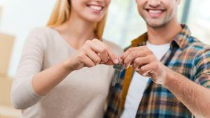 Keys of their new apartment. Cropped image of young loving couple holding keys and smiling while standing in their new house