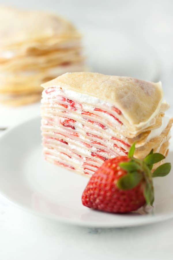 Slice of strawberry crepe cake, with a strawberry in the foreground.