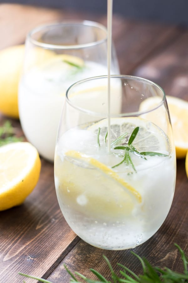 Pouring the cream into a cup of rosemary lemon cream soda.