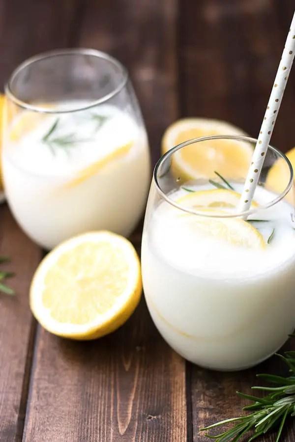 Two glasses of rosemary lemon cream soda garnished with sliced lemons and fresh rosemary.