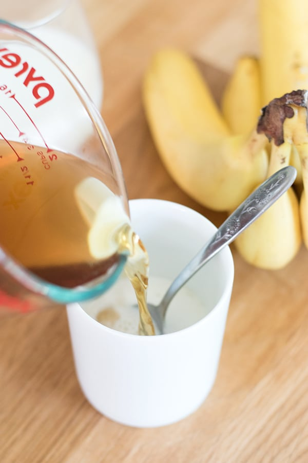 Pouring chamomile tea into a cup of banana milk.