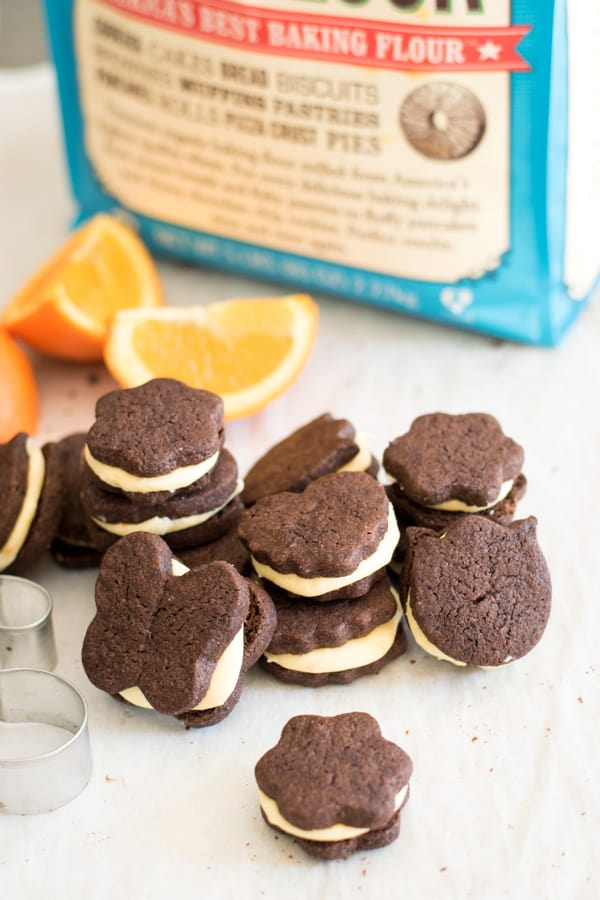 Chocolate orange sandwich cookies stacked up with orange slices and Bob's Red Mill flour in background