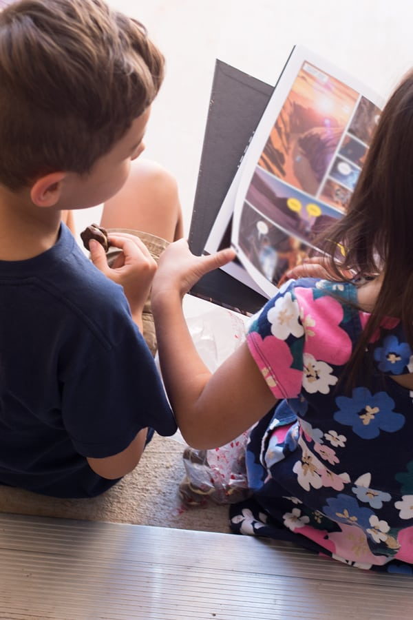 Kids reading book while eating chocolate orange sandwich cookies.