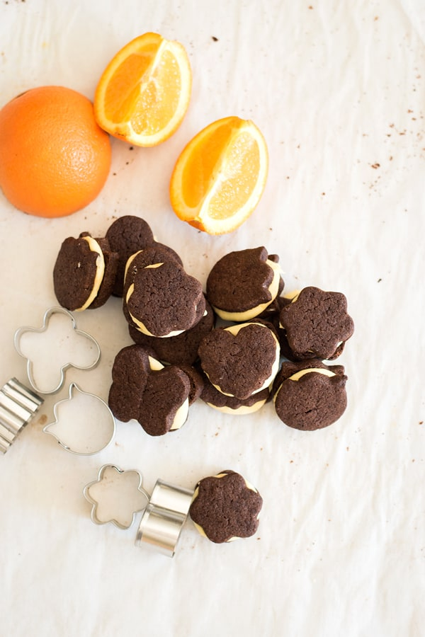 Top view of chocolate orange sandwich cookies with sliced oranges and mini cookie cutters.