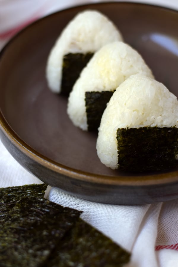 3 tuna mayo onigiri lined up with some seaweed on the side.