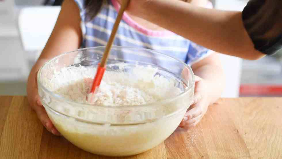 Holding mixing bowl and stirring in flour with a rubber spatula