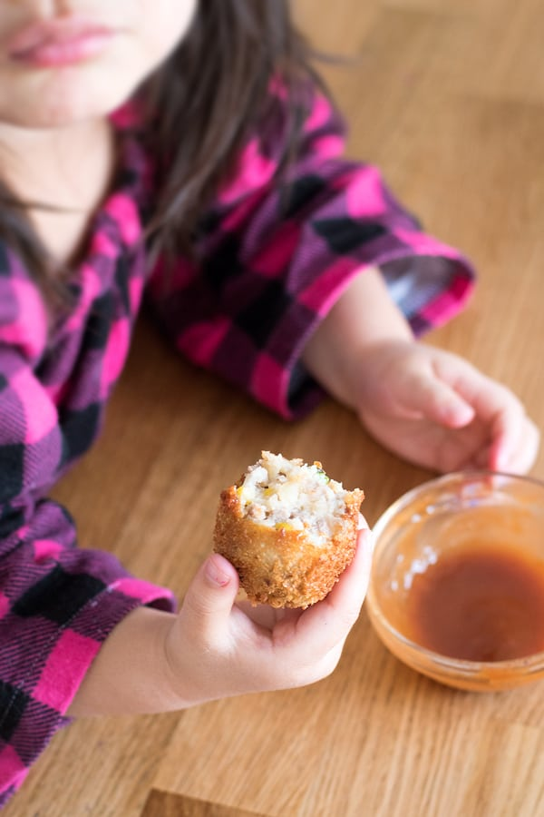 Little girl holding a round korokke, with tonkatsu sauce.