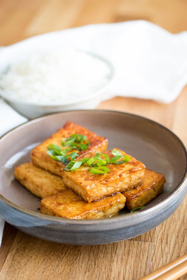 Plate of soy sauce and butter glazed tofu, garnished with sliced green onion, and with a bowl of rice.