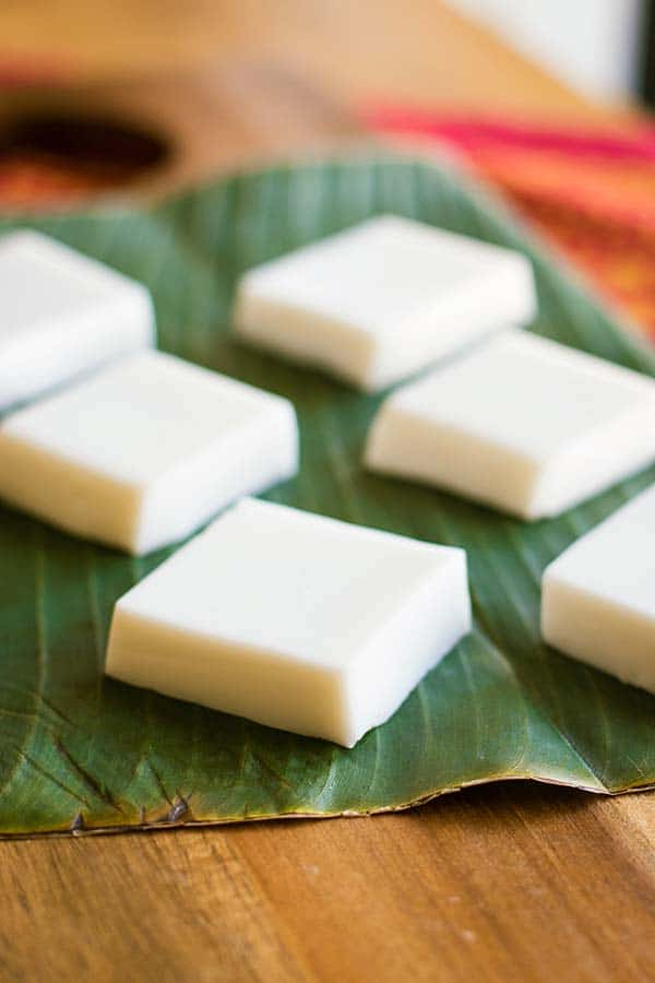 Haupia squares placed on a banana leaf.