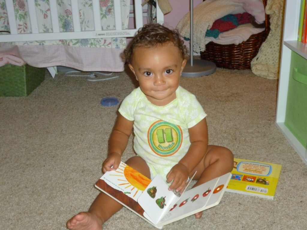 mixed race 11 month old baby turning pages in a book