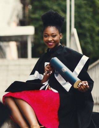 black woman in graduation robe holding diploma