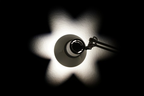 black and white image of lamp turned toward a wall creating a white spotlight``