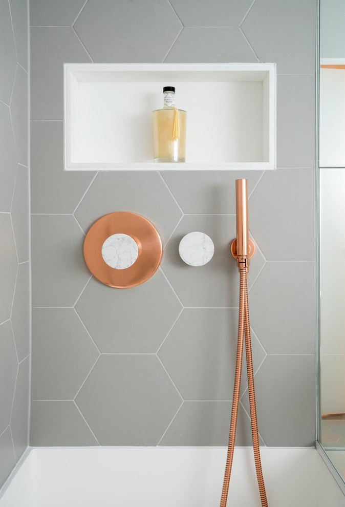 This bathroom features copper and marble fixtures next to light gray hexagon tiles  CONTEMPORIST