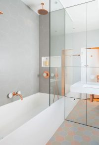This bathroom features copper and marble fixtures next to ...