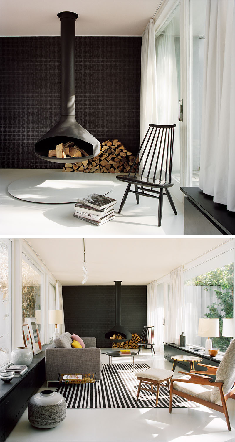 A Hanging Fireplace And Black Accent Wall Stand Out In This
