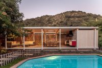 This modern backyard pool house is designed for ...
